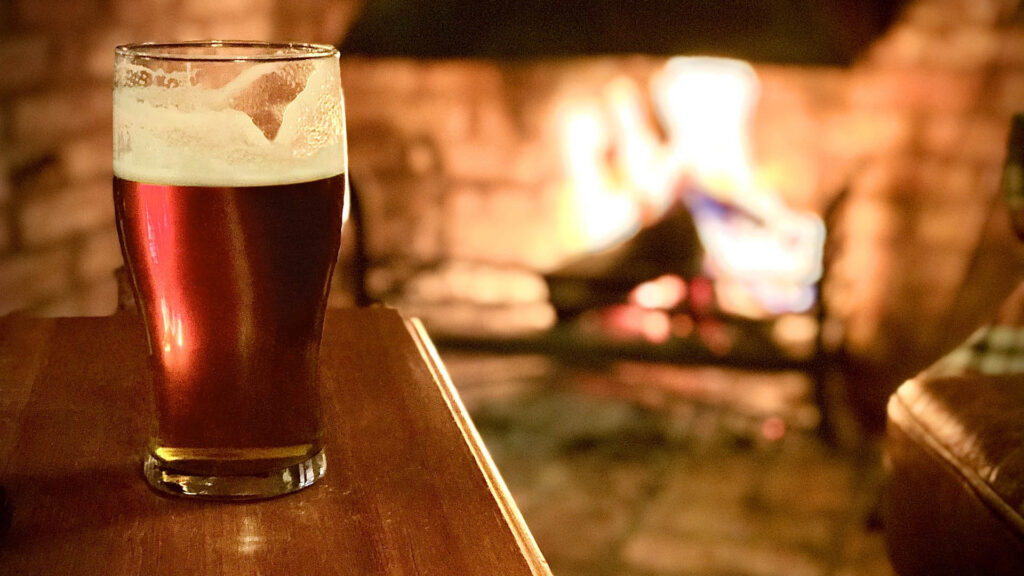 A pint of beer with a fireplace in the background - a traditional pub is the perfect thing to do in London on a rainy day!