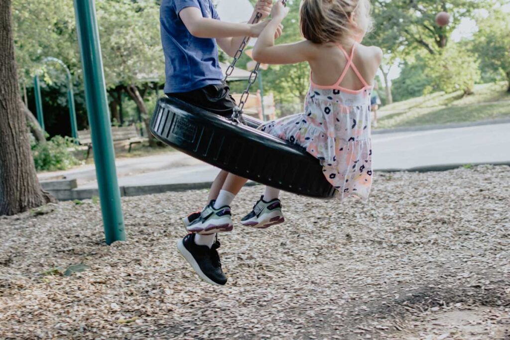 Children play on a tyre swing in London playground
